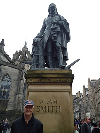 Patrick Grady standing in front of statue of Adam Smith in Edinburgh, Scotland